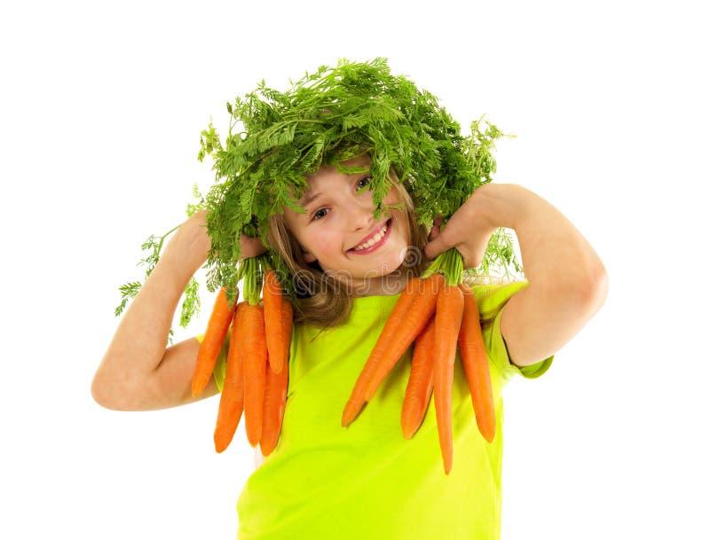 美丽的小女孩用红萝卜 免版税库存图片