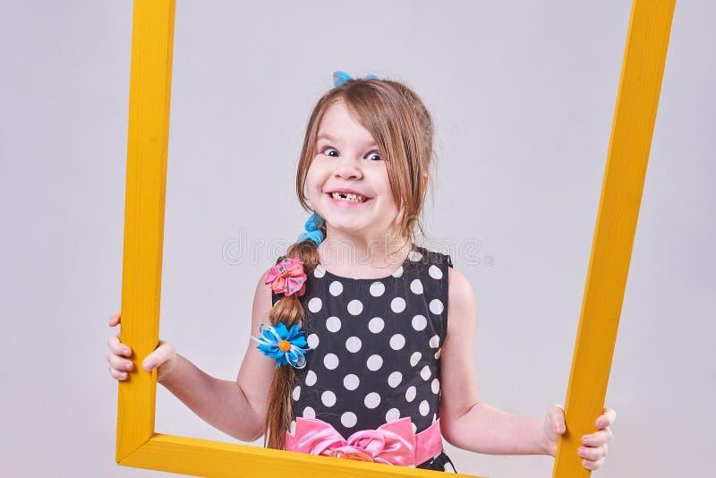 美丽的小女孩,有在他的面孔的一个滑稽的表示的,拿着一个黄色框架 库存照片