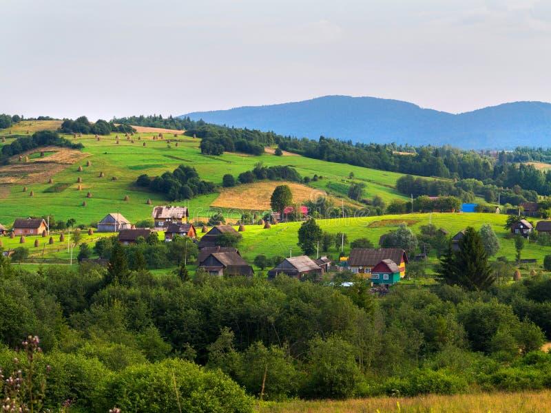 美丽的小村庄 在距离您能看到干草堆 并且所有这反对山的背景 免版税库存图片