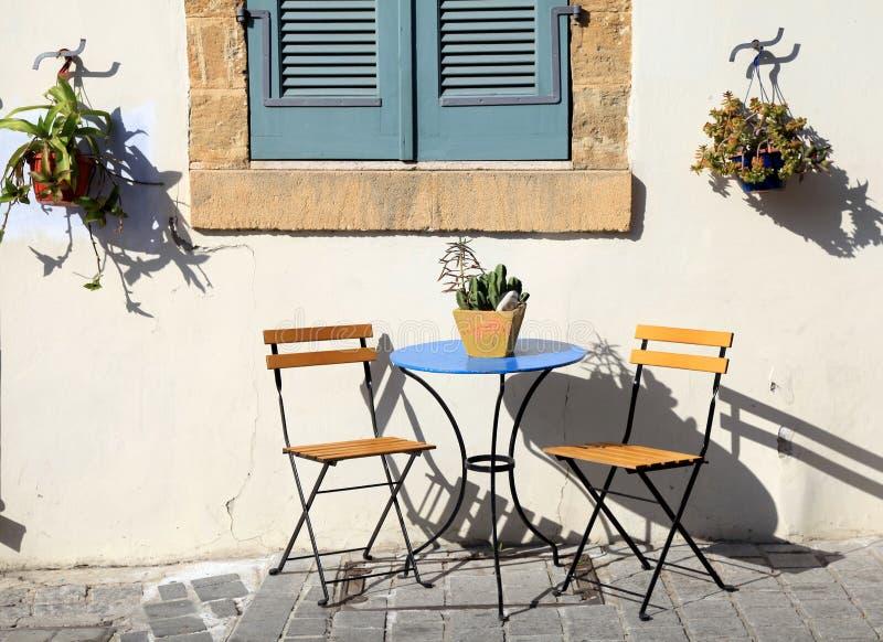 美丽的小椅子和一张桌在边路在塞浦路斯 库存图片