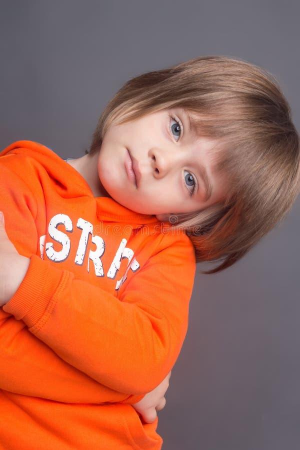 美丽的小男孩特写镜头画象四岁,穿橙色有冠乌鸦 库存图片