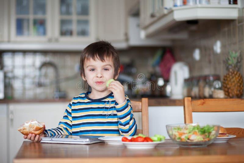 美丽的小男孩,在家吃三明治 免版税库存图片