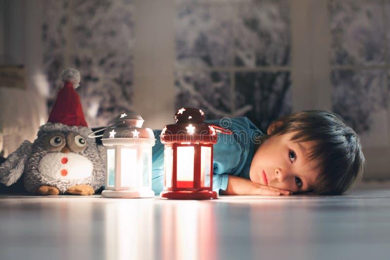 美丽的小男孩,躺下在地板上,看蜡烛 免版税图库摄影