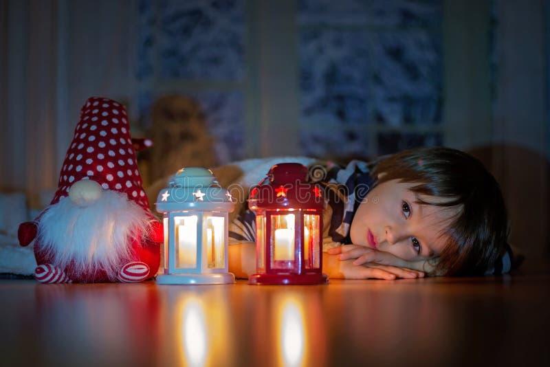 美丽的小男孩,躺下在地板上,看蜡烛 库存图片