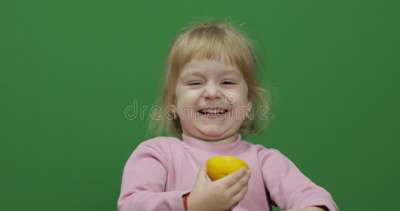 美丽的少女吃与一副鬼脸的一个柠檬在她的面孔 o 库存图片
