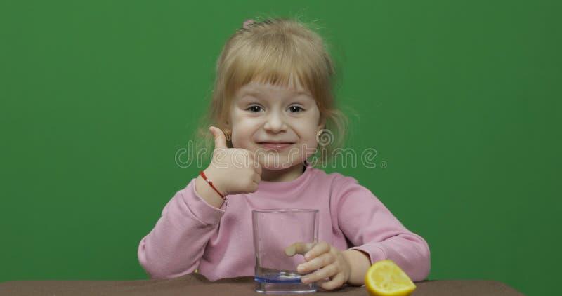 美丽的少女吃与一副鬼脸的一个柠檬在她的面孔 o 库存照片