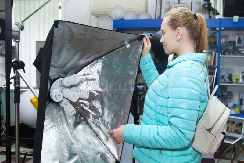 美丽的少女在专业照片设备商店选择永久演播室照片光灯与方形的反射器的 库存图片