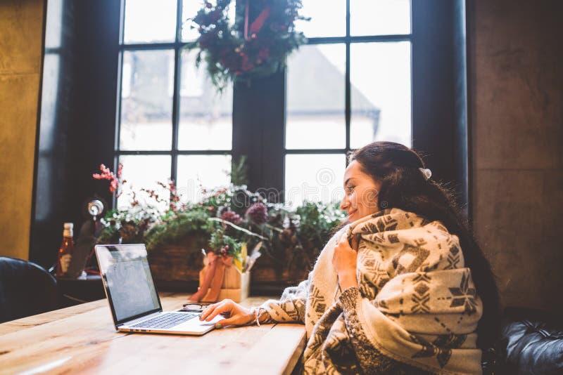 美丽的少女在冬天使用膝上型计算机技术,类型发短信给看在咖啡馆的显示器由窗口在木桌上, 免版税库存照片