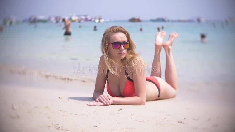 美丽的少女在海滩说谎,穿红色比基尼泳装 热带假期 图库摄影