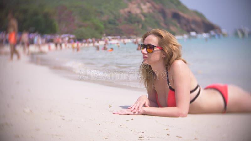 美丽的少女在海滩说谎,穿红色比基尼泳装 热带假期 库存图片