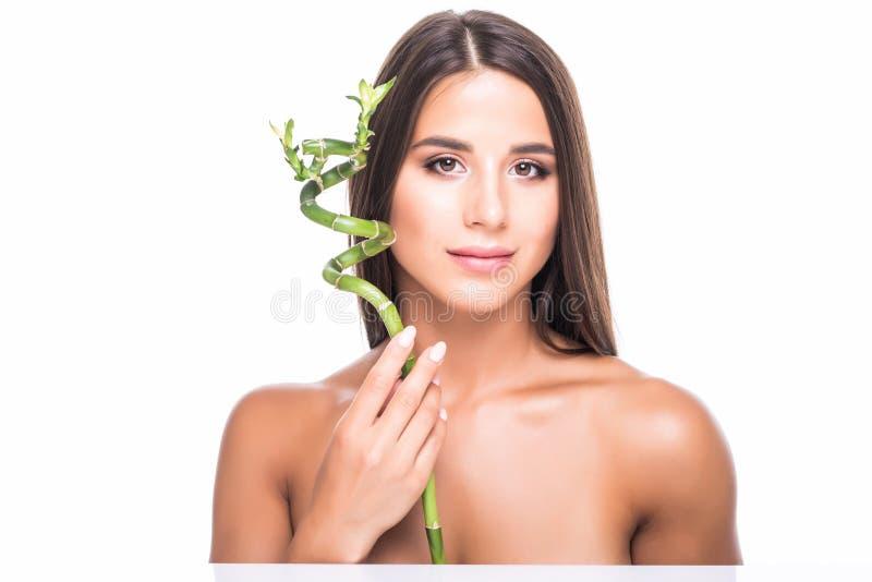 美丽的少女在白色背景的演播室在手上拿着一片绿色热带叶子并且报道她的面孔的部分 免版税库存图片