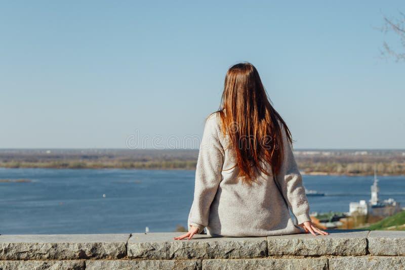 美丽的少女坐伏尔加河堤防 免版税库存照片