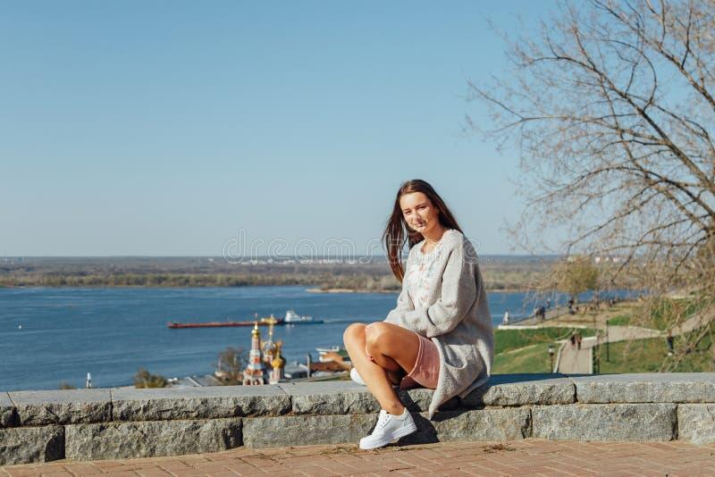 美丽的少女坐伏尔加河堤防 免版税库存图片