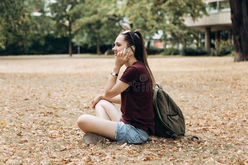 美丽的少女谈话在一个手机 库存图片
