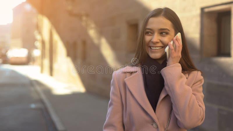 美丽的少女谈话在电话,走在古城街市,漫游 免版税库存图片