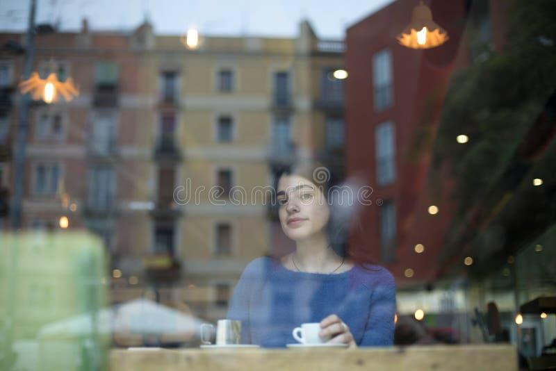 美丽的少女饮用的咖啡和看照相机画象通过玻璃,当坐在咖啡馆时的桌上 图库摄影
