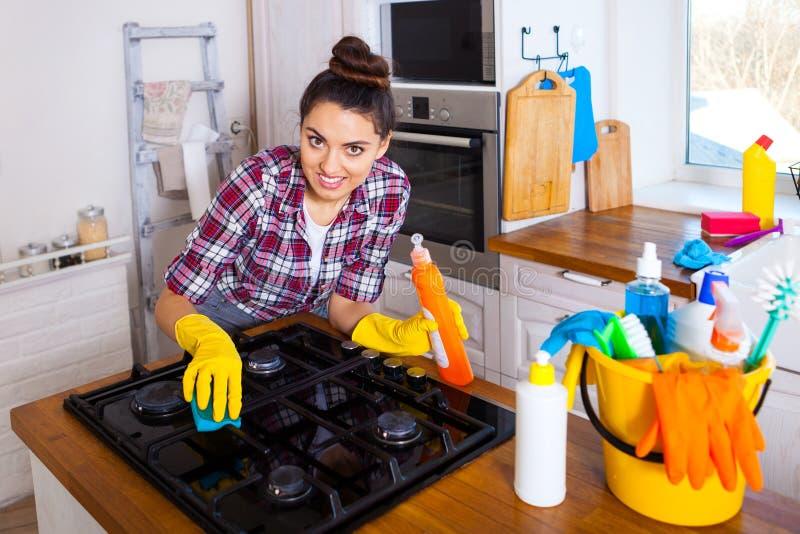 美丽的少妇做清洗房子 女孩清洁ki 免版税库存图片