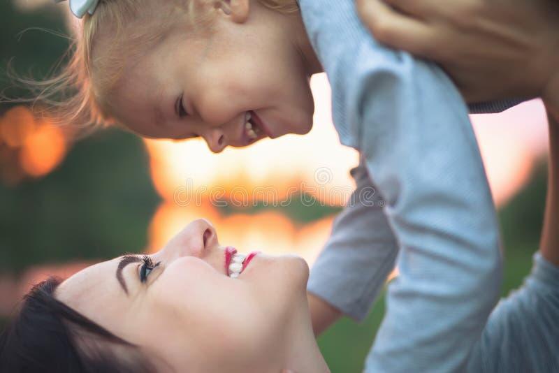美丽的少妇和她迷人的矮小的女儿拥抱 库存图片