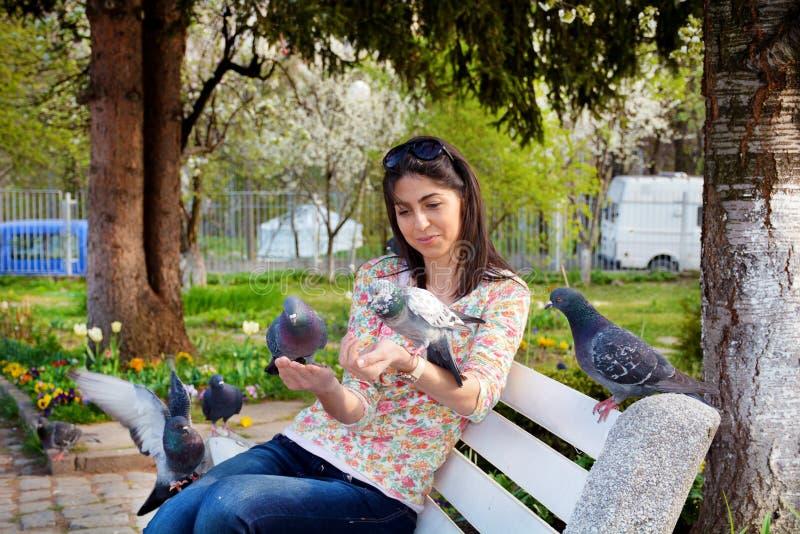 美丽的少妇哺养的鸽子在春天庭院里 免版税库存图片