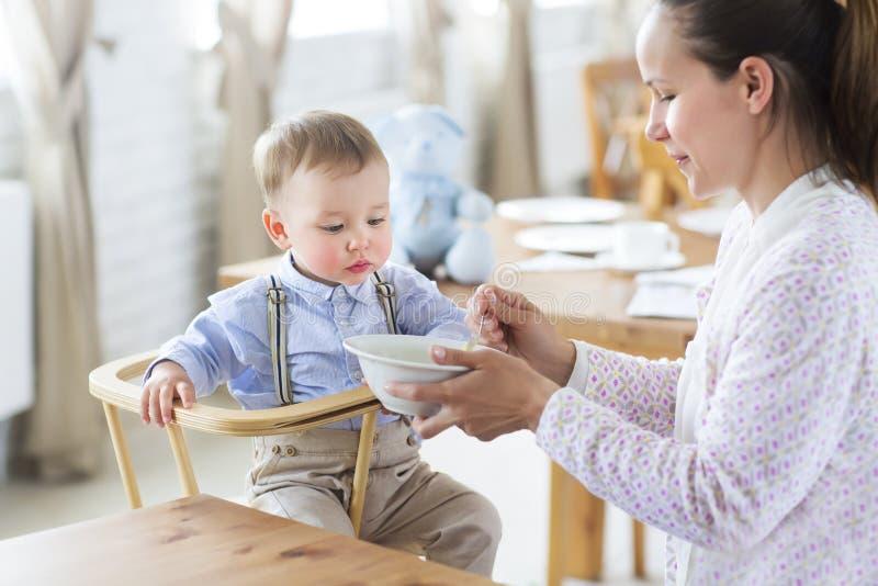 美丽的少妇喂养她的小儿子 免版税库存照片