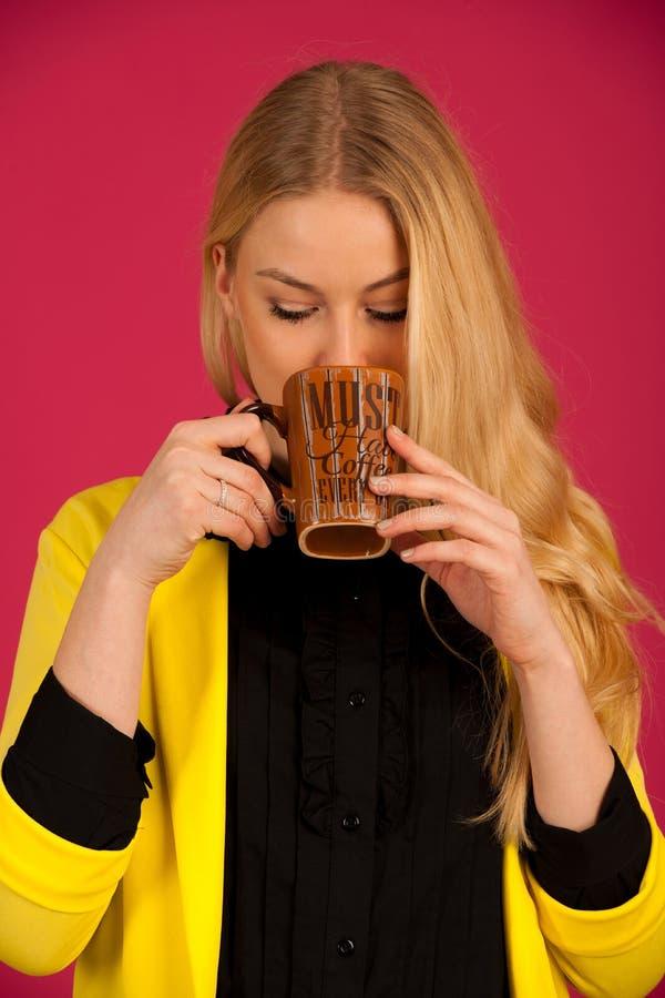 美丽的少妇喝在桃红色背景的coffe 免版税图库摄影