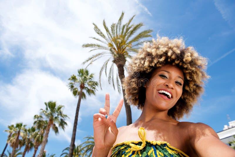 美丽的少妇在度假在采取selfie和打手势和平标志的海滩的 库存照片