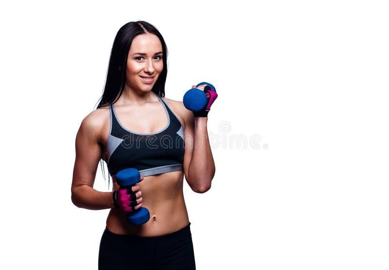 美丽的少妇在演播室做与哑铃的锻炼 举重量的运动的运动女孩反对白色背景 免版税库存照片