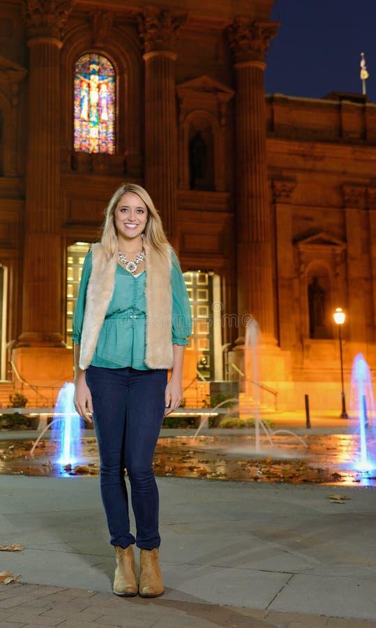 美丽的少妇在都市风景前面站立在晚上 图库摄影