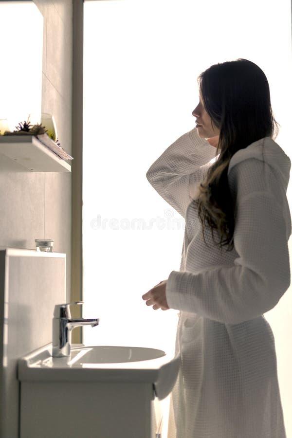 美丽的少妇在面对镜子和水槽的早晨 免版税库存照片