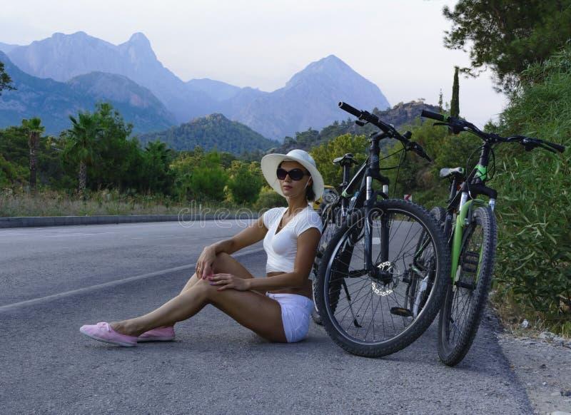 美丽的少妇坐在路边缘 库存照片