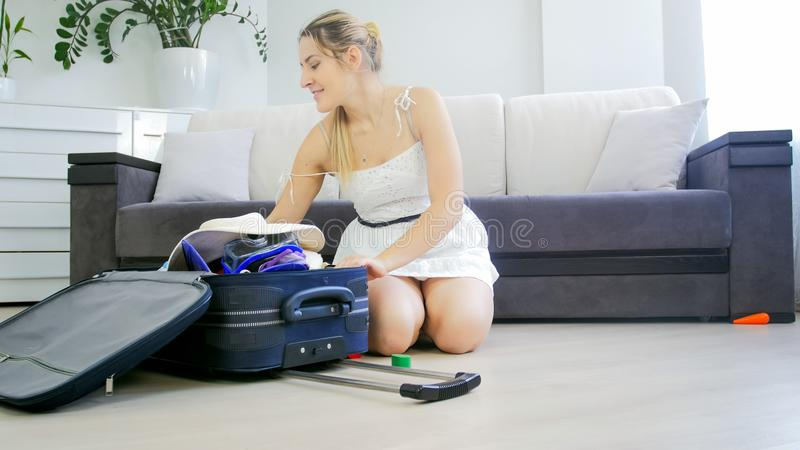 美丽的少妇坐地板和包装的事为暑假 免版税库存照片