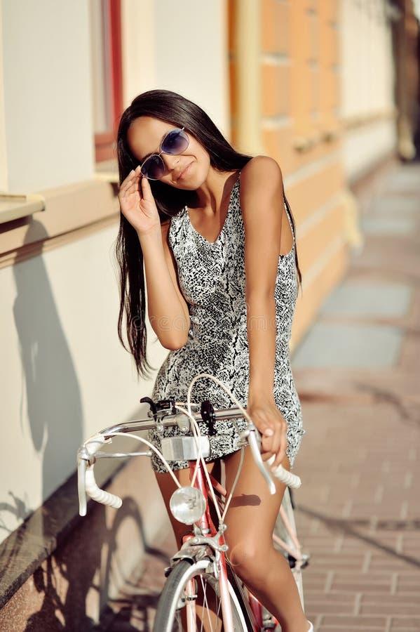 美丽的少妇坐她的自行车 免版税库存照片