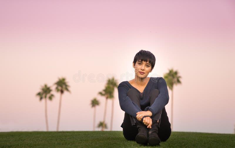 美丽的少妇坐小山在日落 库存照片
