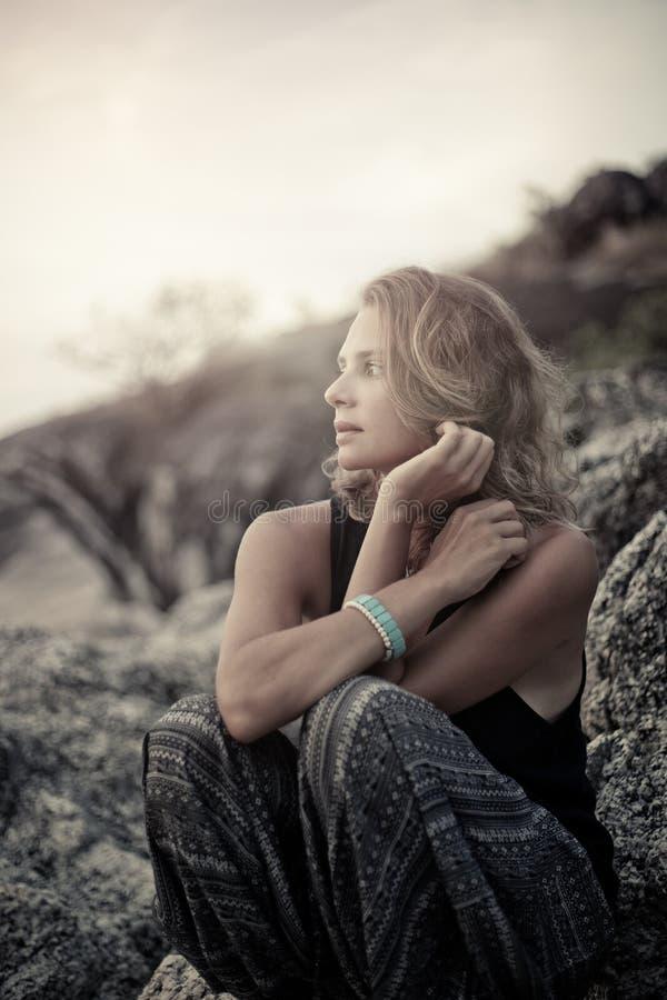 美丽的少妇坐岩石在日落 库存图片
