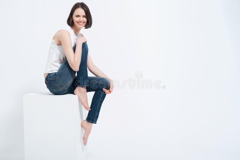 美丽的少妇坐白色立方体在演播室 免版税库存照片