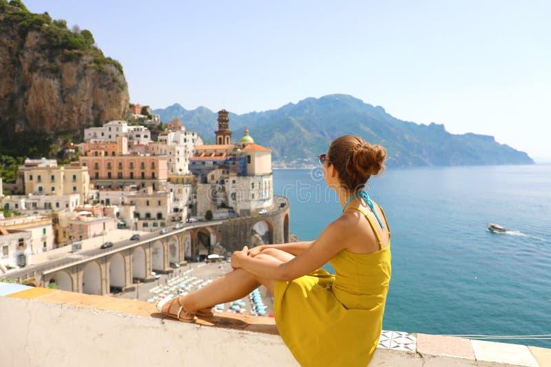 美丽的少妇坐看阿特拉尼的惊人的全景村庄阿马尔菲海岸的,意大利墙壁 免版税库存照片