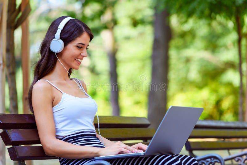 美丽的少妇坐长凳在公园,使用便携式计算机 免版税库存图片