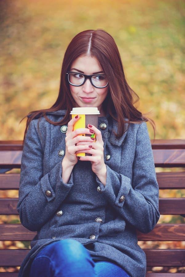 美丽的少妇坐长凳饮用的咖啡或热的茶在春天享用在公园的秋天外套室外 库存图片