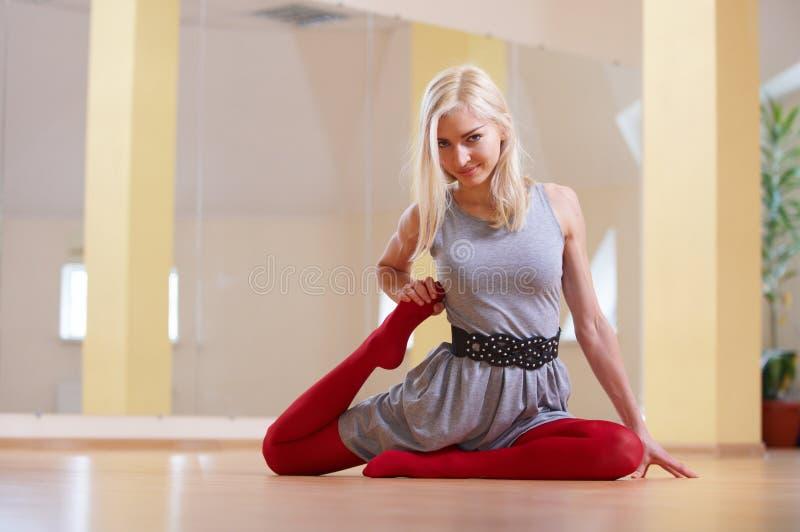 美丽的少妇实践瑜伽asana Pigeon国王姿势rajakapotasana在健身屋子 免版税图库摄影
