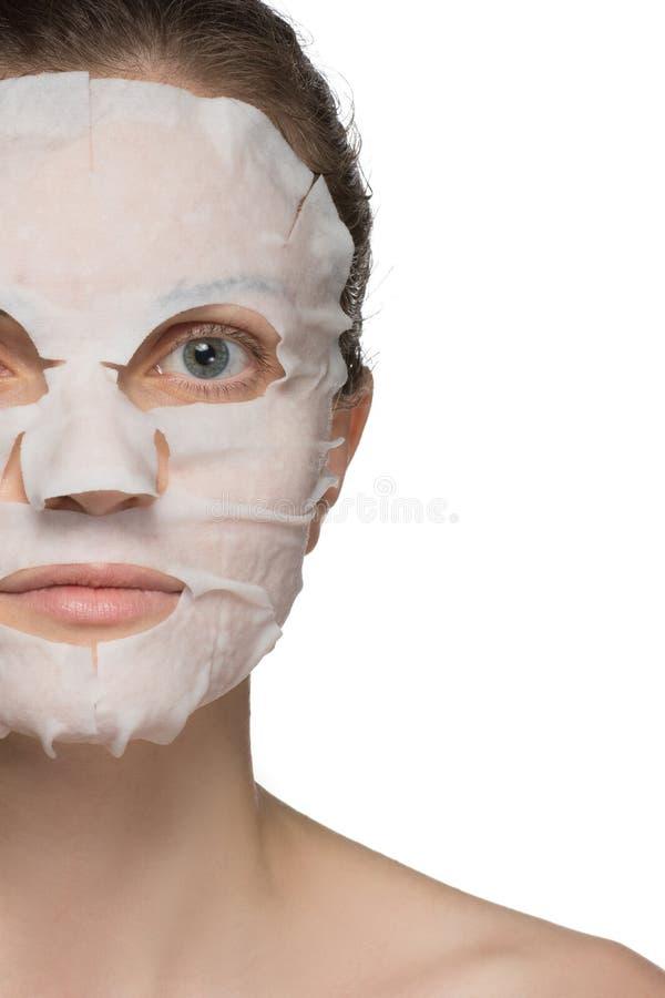 美丽的少妇应用在一张面孔的一个化妆面具在a 免版税图库摄影