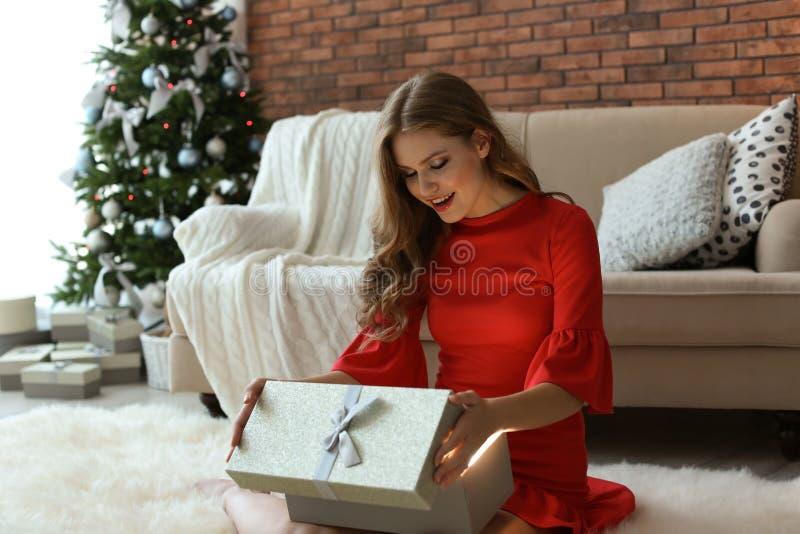 美丽的少妇开头礼物盒在家 免版税库存照片