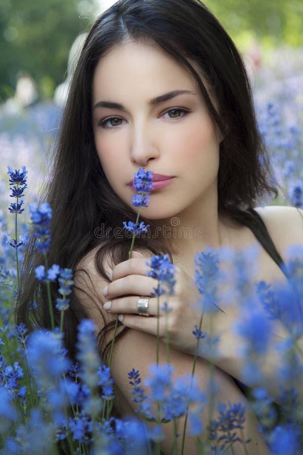 美丽的少妇我蓝色花田 库存图片