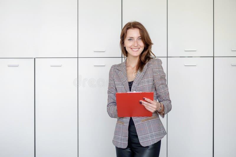 美丽的少妇拿着一个文件夹,看照相机并且微笑着,当站立在办公室时 图库摄影