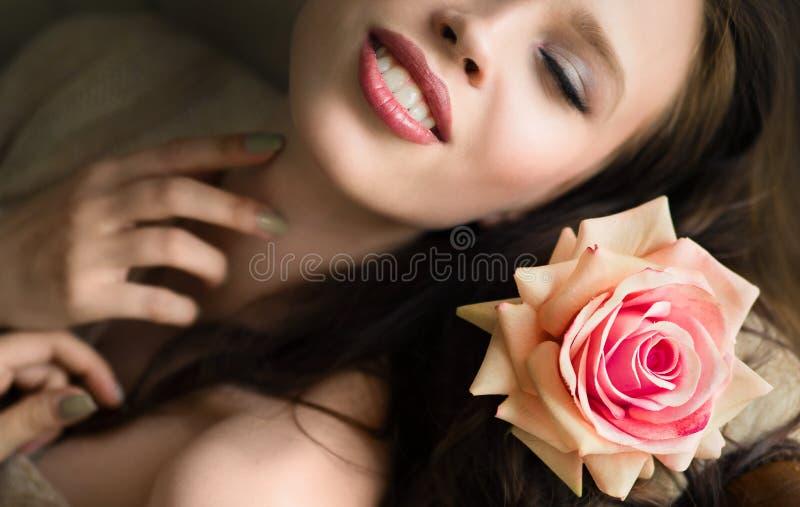 美丽的少妇接近的画象在床上与上升了 免版税库存图片