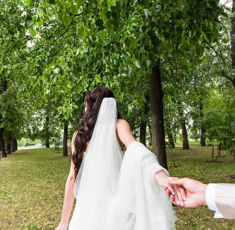 美丽的少妇新娘握一个人的手户外 跟我学 免版税库存照片