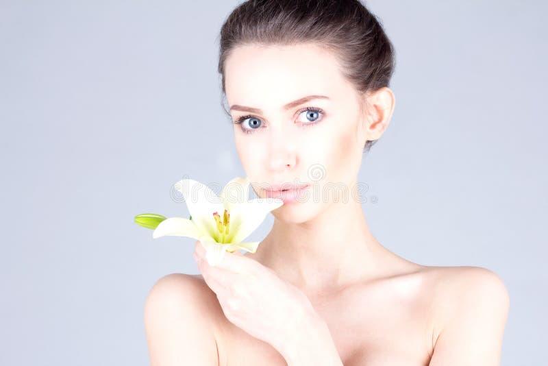美丽的少妇有一个百合的在她的手上和有大蓝眼睛的 温泉和秀丽 库存照片