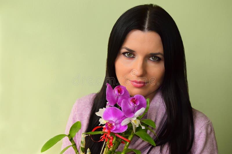 美丽的少妇有嫉妒和一朵桃红色兰花的浅黑肤色的男人 免版税库存图片