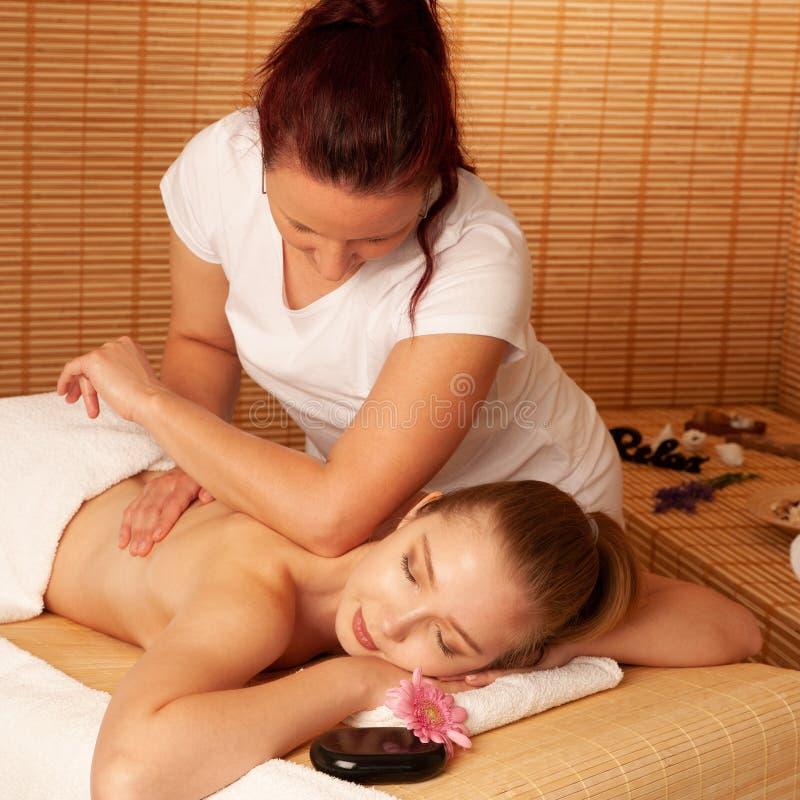 美丽的少妇有按摩治疗在温泉沙龙-健康 免版税库存图片