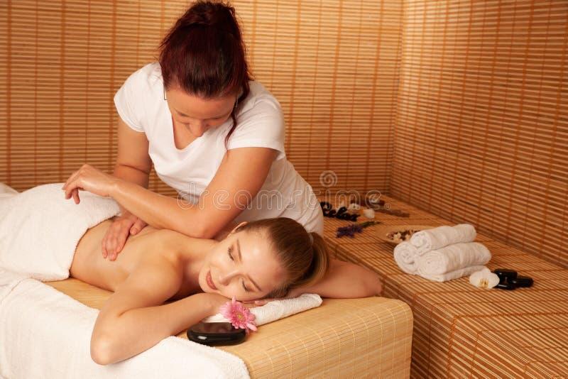 美丽的少妇有按摩治疗在温泉沙龙-健康 免版税库存照片