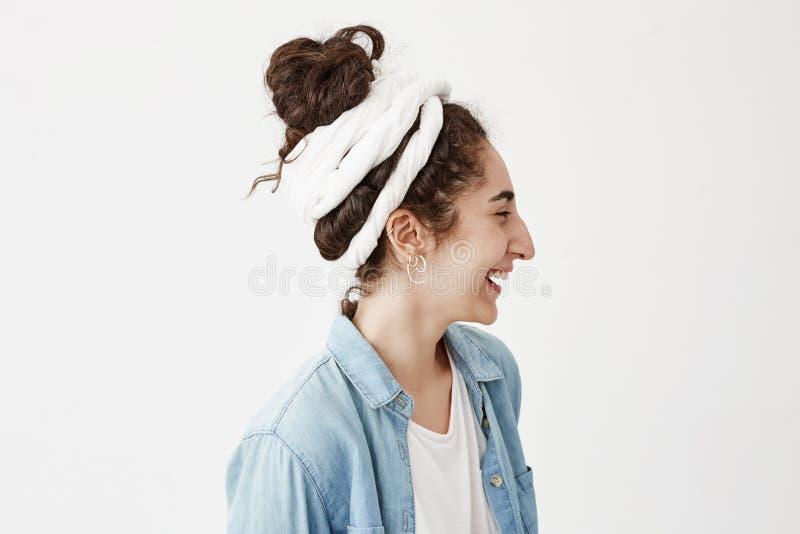 美丽的少妇档案做旧布和时髦牛仔布衬衣的,放松户内,看与俏丽的微笑 免版税库存图片